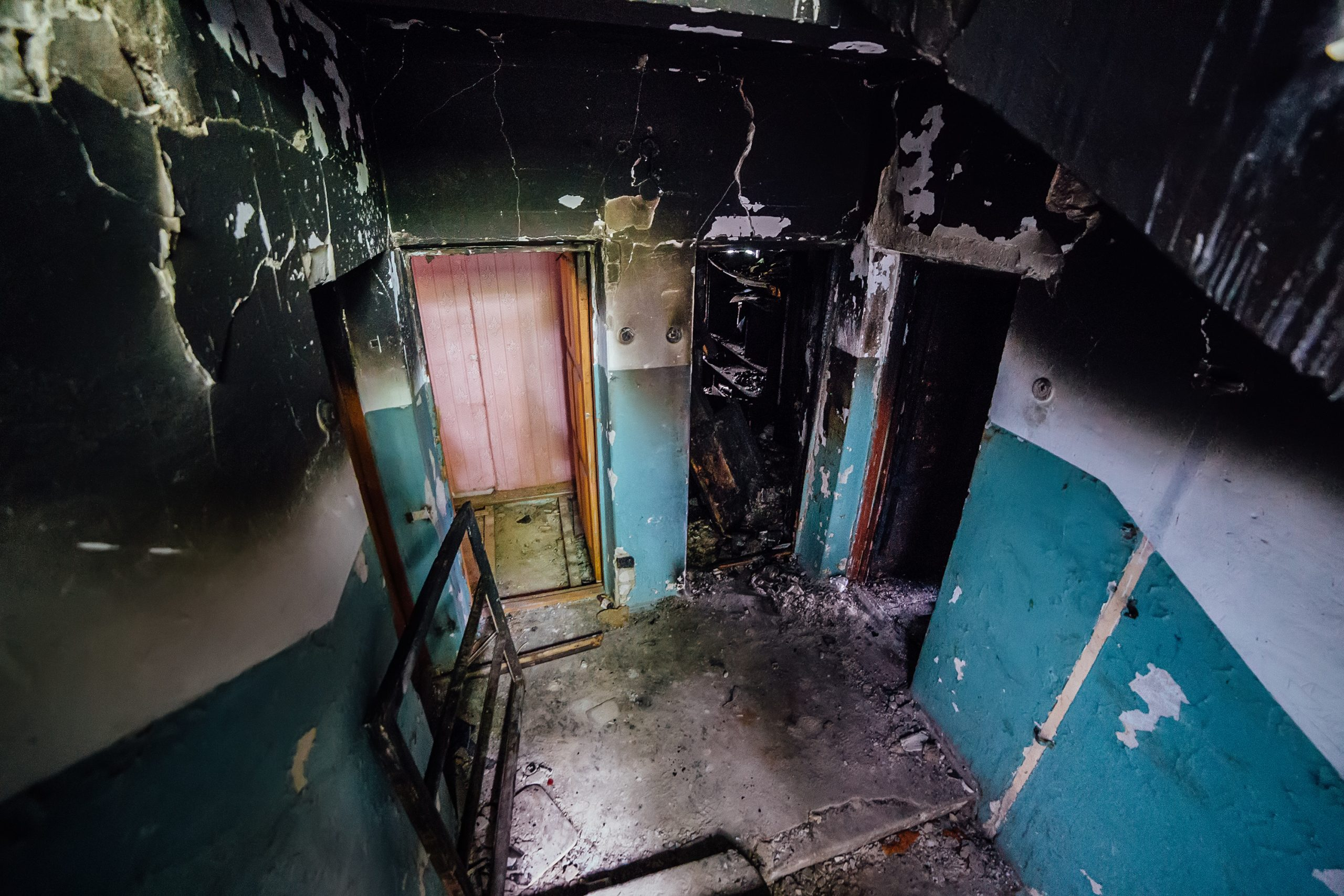 Consequences of fire in apartment building. Burnt staircase and doors, charred walls.
