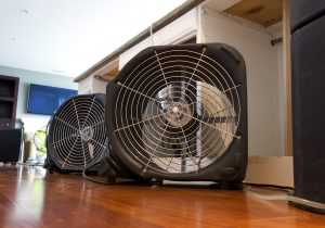 fans running to dry water damaged floors in residential home from flooding