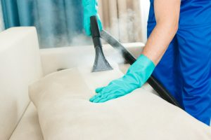 An employee of a cleaning company provides a chemical and steam cleaning service for the sofa. Steam cleaner